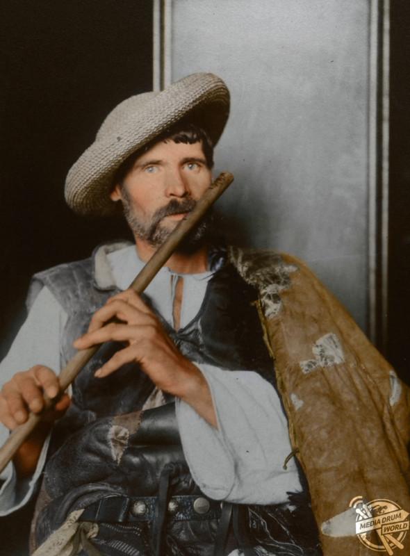 A Romanian piper in a sheepskin cloak, c1910.