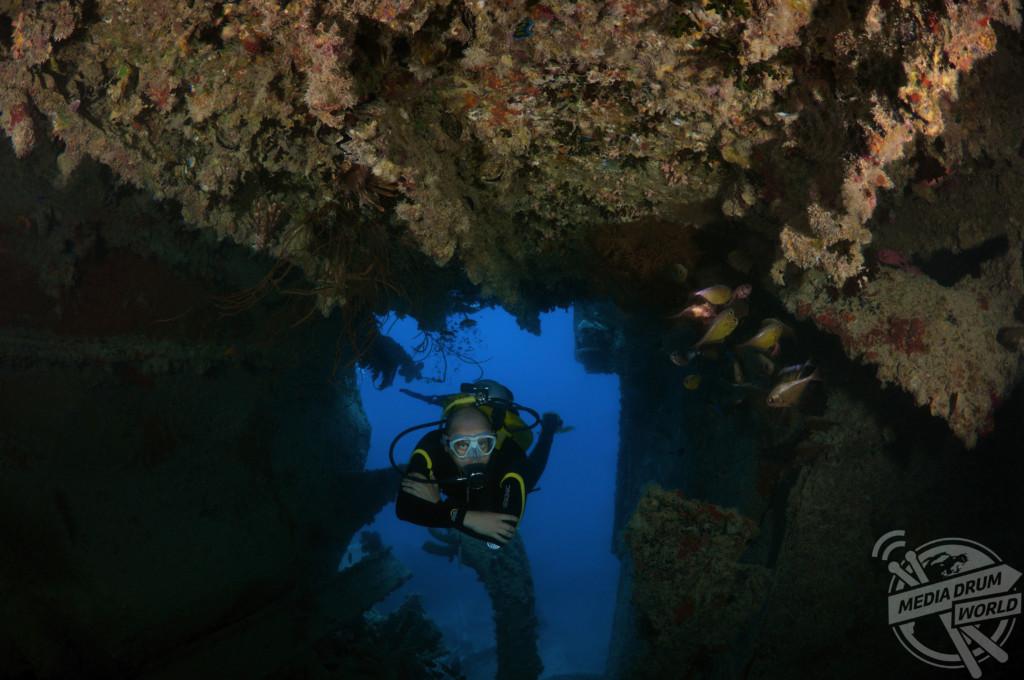 A scuba diver swimming through the wrecked ship.