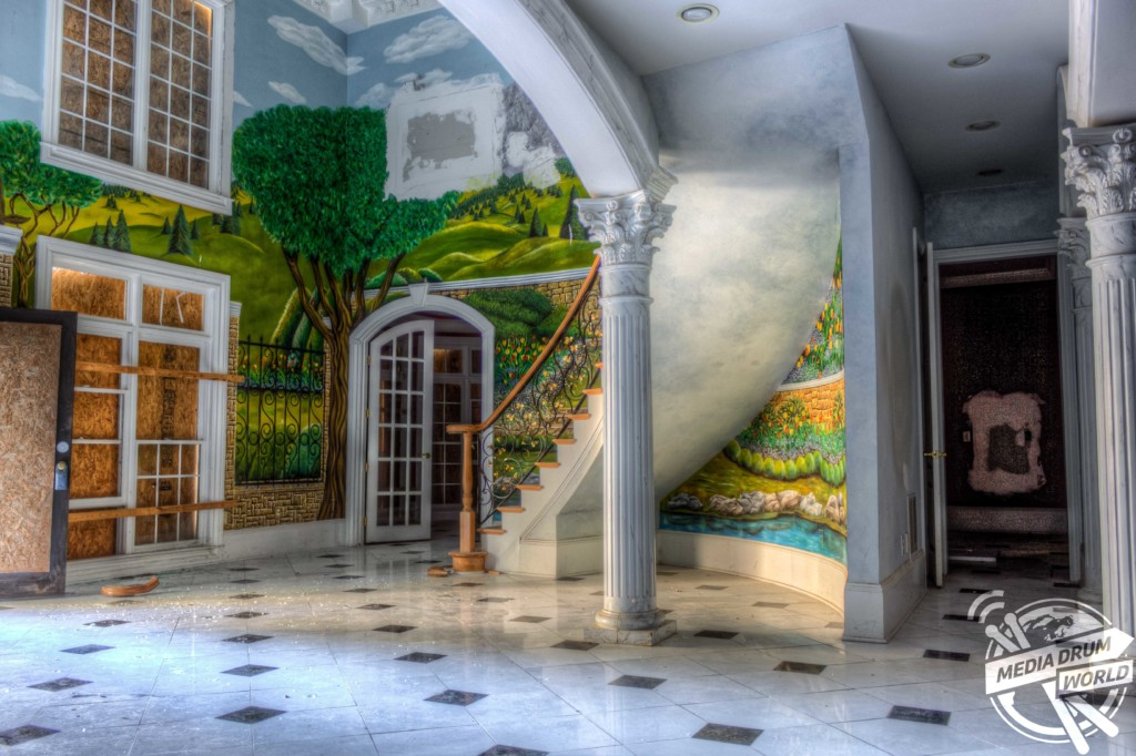 WOODSTOCK, GEORGIA, USA: A brightly coloured mural accompanying the staircase. EERIE images of a once multi-million-dollar mansion which would not look out of place in Al Pacino's Hollywood film Scarface have been captured. The series of chilling pictures show how the previous owner's taste in gaudy green countryside and gondola murals illuminate the walls. Other photos show a decrepit and drained outdoor swimming pool that has seen brighter days. The mansion's grand staircase centrepiece has also been snapped – not dissimilar to those in the infamous Scarface shootout scene. The mansion's backyard also stands still and overgrown and the windows are heavily boarded up. The spectacular shots were taken by American photographer Jeff Hagerman in Woodstock, Georgia. Jeff Hagerman / mediadrumworld.com