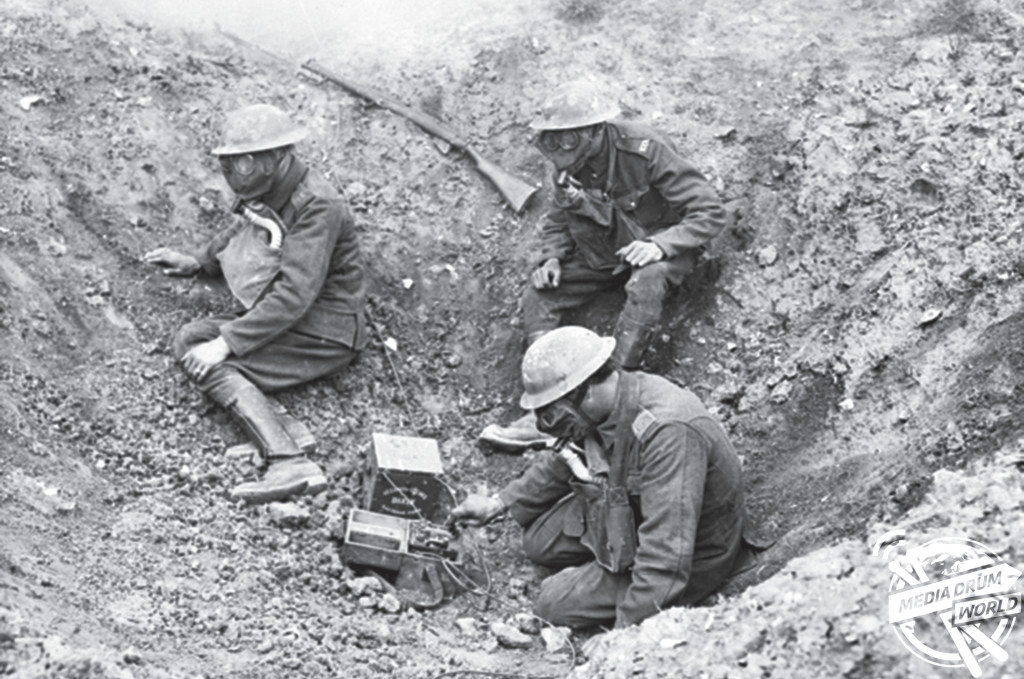 Three members of the British signal service wearing gas masks in a shell hole during a gas attack. Matthew Leonard / mediadrumworld.com