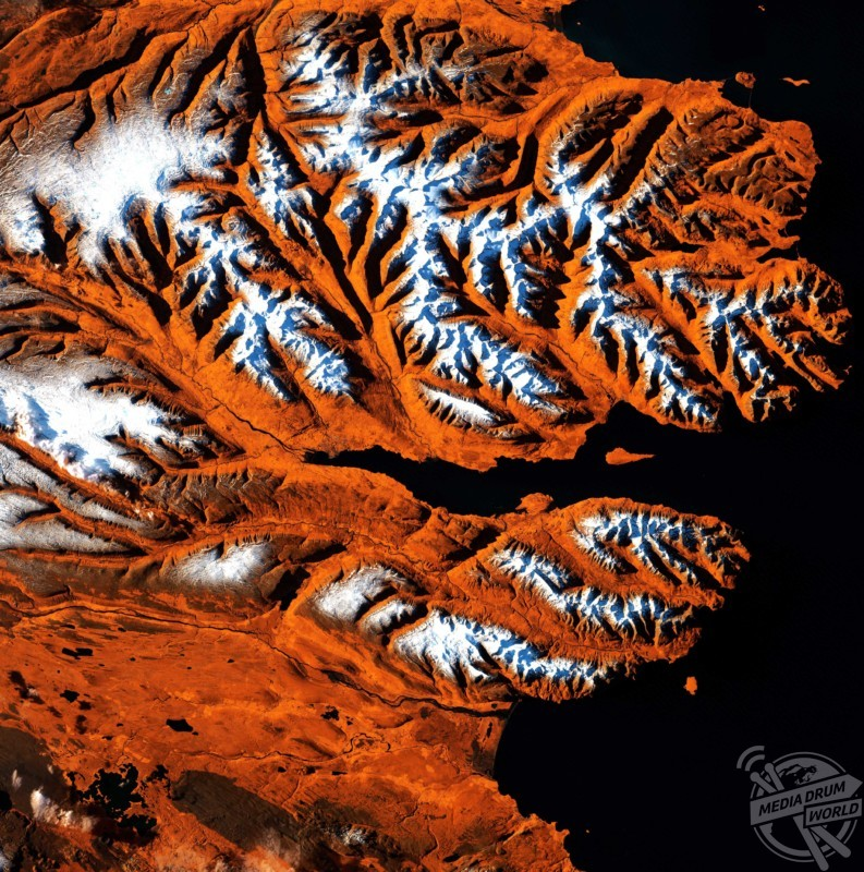 Icelandic fjords, satellite image. This area of Iceland's northern coast is centred on the Eyjafjordur, a deep fjord that juts into the mainland between steep mountains. At its mouth is the small Hrisey Island. The ice-free port city of Akureyri lies near the fjord's narrow tip, and is Iceland's second largest city after the capital Reykjavik.  US Geological Survey / SPL / mediadrumworld.com