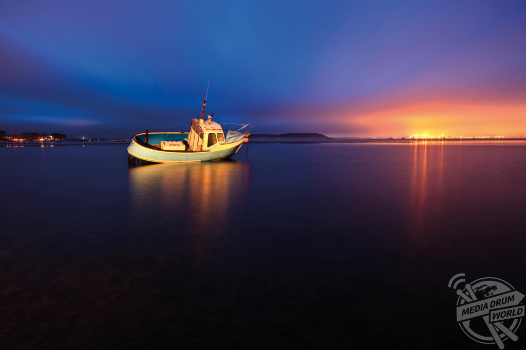 Poole Harbour at twilight with the town of Poole in the background. A torch was used to paint light onto the boat.  Mark Bauer / mediadrumworld.com