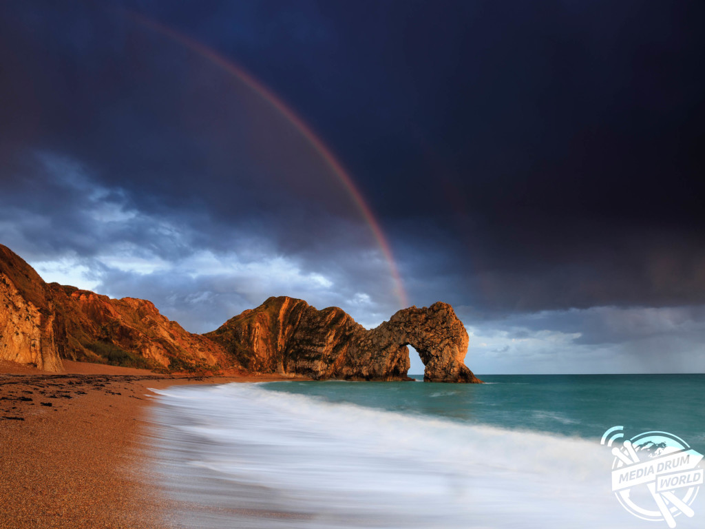 The 'classic' view of Durdle Door from the beach, with the warm glow of the evening sun and a rainbow to set it off.  Mark Bauer / mediadrumworld.com
